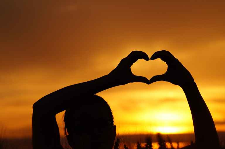 silhouette woman hand holding heart shape against orange sky